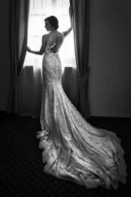 Stylizovaná černobílá fotografie nevěsty, krátce po obléknutí svatebních šatů.