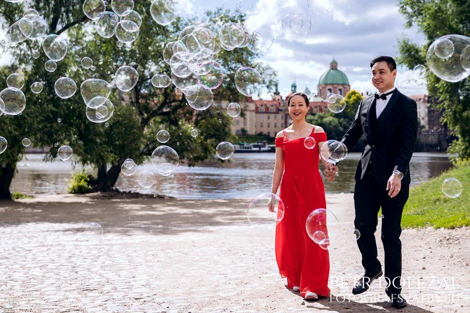 Pre Wedding Photo with bubbles at Vltava riverside and Charles Bridge in background