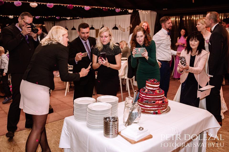 svatební hosté si fotí svatební dort svými mobily