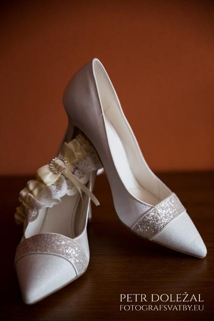 svatební detail podvazku a střevíců nevěsty