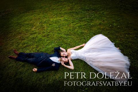 Ženich a nevěsta ležící na trávě