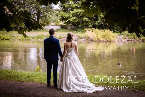 svatební fotografie - vodní hladina, novomanželé zády k fotografovi