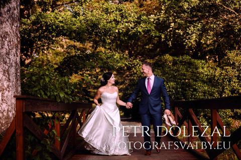Svatební pár běžící po mostu