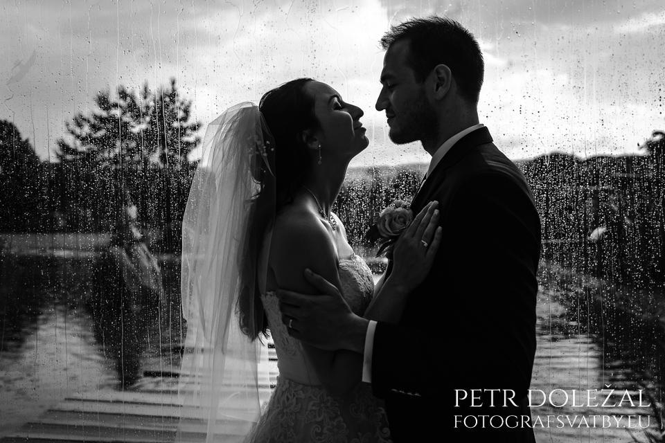 Když prší štěstí... Nevěsta se ženichem před skleněnou stěnou, ze které stékají kapky deště... Opět černobílá svatební fotografie.