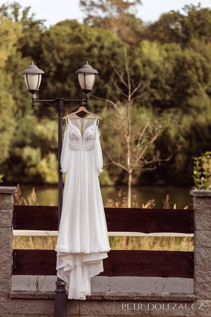 Svatební šaty pověšené v areálu Štiřínské stodoly